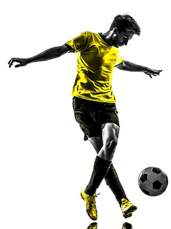 one brazilian soccer football player young man dribbling in silhouette studio  on white background photo