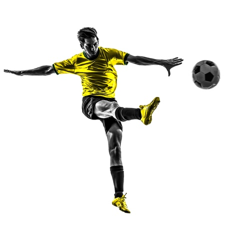 kicking ball: one brazilian soccer football player young man kicking in silhouette studio  on white background