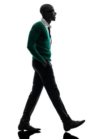 シルエット スタジオ白い背景の上を歩いて 1 つのアフリカ系黒人男性