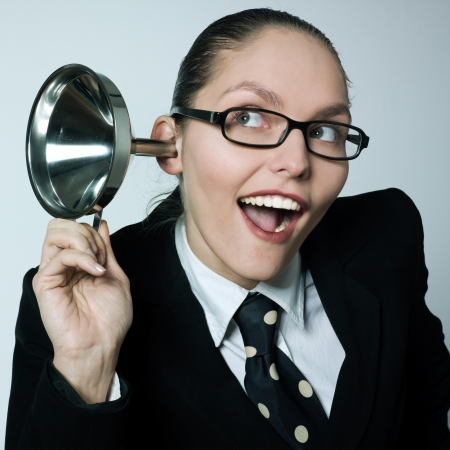 studio shot portrait of one caucasian curious business woman  hearing aid funnel curious spying gossip Stock Photo
