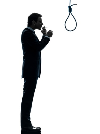 man smoking: one caucasian man smoking cigarette  standing in front of hangmans noose in silhouette studio isolated on white background Stock Photo