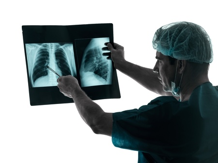 one caucasian man doctor surgeon radiologist medical examining lung torso  x-ray image silhouette isolated on white background Stock Photo - 20012001