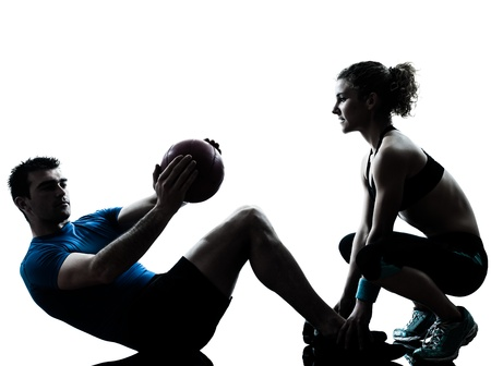 fitness trainer: one caucasian couple man woman personal trainer coach exercising weights fitness ball silhouette studio isolated on white background Stock Photo