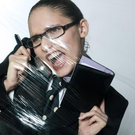 suffocating: studio shot ritratto di donna d'affari sotto pressione al telefono