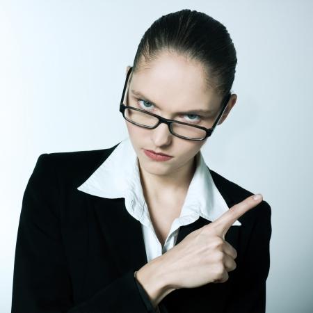 tough woman: studio shot portrait of one beautiful business strict  nanny teacher woman pointing Stock Photo