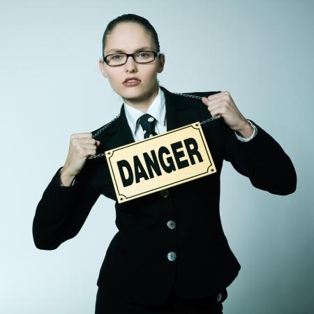 arrogancia: tiro del estudio retrato de una joven caucásica peligrosa mujer de negocios mujer con una señal de peligro