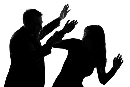 beaten woman: one caucasian couple man and woman expressing domestic violence in studio silhouette isolated on white background Stock Photo