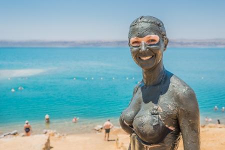 una mujer caucásica de aplicar el tratamiento de cuidado del fango del mar muerto en Jordania