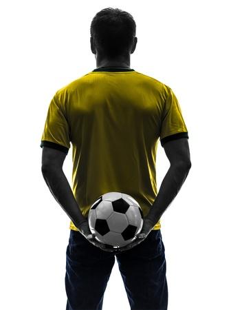 football silhouette: uno caucasico uomo azienda calcio calcio, silhouette, vista posteriore di nuovo in silhouette su sfondo bianco Archivio Fotografico