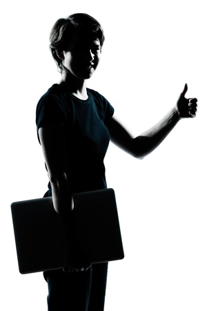 one caucasian young teenager silhouette girl holding carrying laptop computer thumb up portrait in studio cut out isolated on white background photo