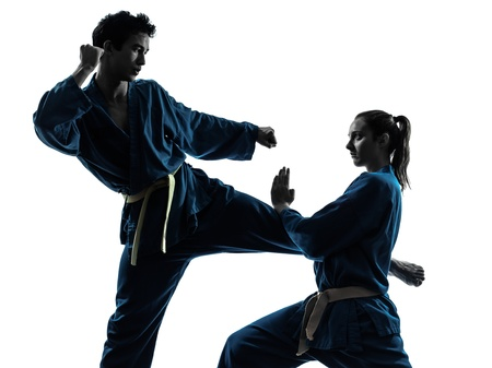 arte marcial: una pareja hombre mujer el ejercicio de karate artes marciales vietvodao en el estudio de la silueta aislado en el fondo blanco