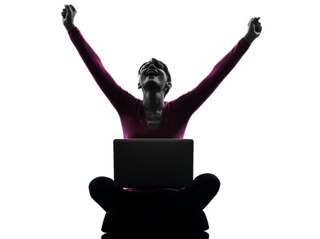 winning woman: one caucasian woman happy winning  computing laptop computer  in silhouette studio isolated on white background