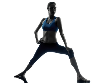 lunges: one caucasian woman exercising yoga warrior position in silhouette studio isolated on white background