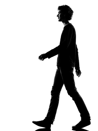 walking down: young man sad walking silhouette in studio isolated on white background
