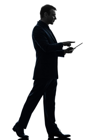 one caucasian business man walking touchscreen digital tablet   in silhouette on white background photo