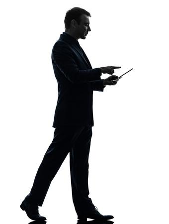 hombre: un hombre de negocios caucásico caminando tableta digital con pantalla táctil en la silueta en el fondo blanco