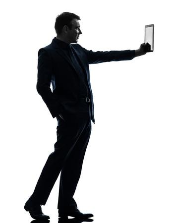 silueta hombre: un hombre de negocios caucásico que sostiene la tablilla digital en silueta sobre fondo blanco Foto de archivo