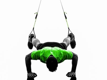 suspension: one caucasian man exercising   suspension training  trx   on white background