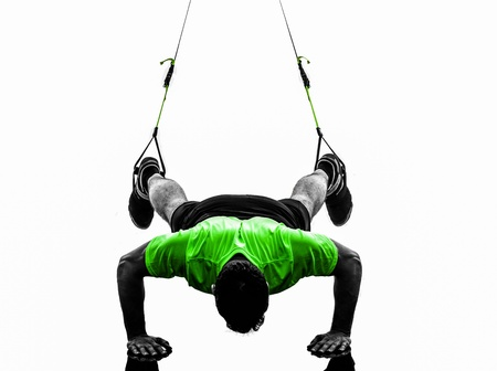 one caucasian man exercising   suspension training  trx   on white background