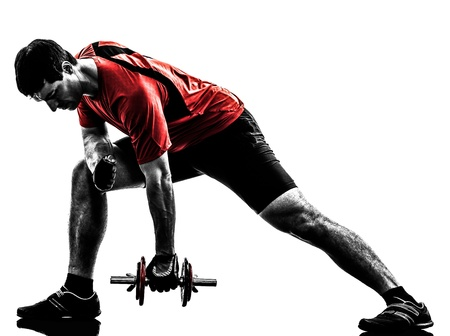 ejercicio aer�bico: un hombre cauc�sico ejercicio de entrenamiento con pesas en el fondo blanco Foto de archivo