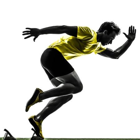 gente corriendo: un hombre cauc?sico joven sprinter corredor en parrilla de salida silueta de estudio sobre fondo blanco Foto de archivo