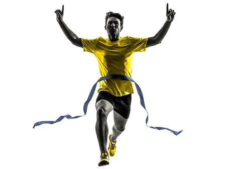 triunfador: un hombre cauc?sico joven sprinter running ganador en la l?nea de meta en estudio de la silueta sobre fondo blanco