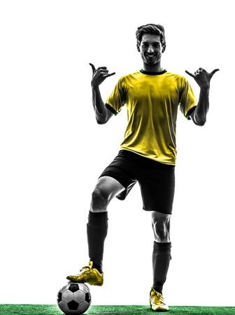 indoor soccer: una brasile�a de f�tbol jugador de f�tbol joven de pie saludando en el estudio de la silueta sobre fondo blanco Foto de archivo