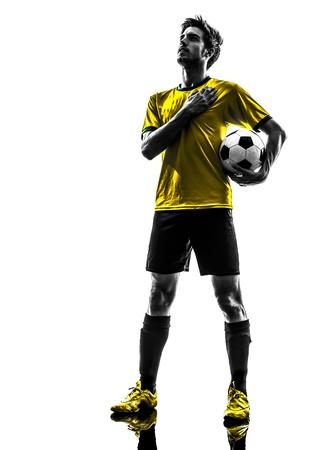 jugador de futbol: una brasile�a de f�tbol jugador de f�tbol joven de pie en el estudio de la silueta sobre fondo blanco Foto de archivo