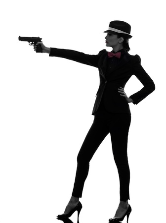 spy girl: one stylish caucasian woman in suit holding gun in silhouette  on white background