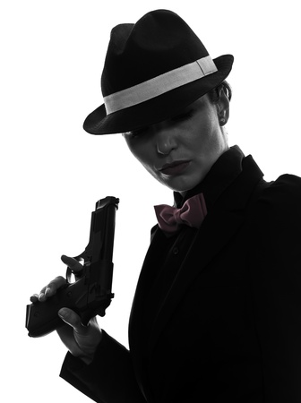 handgun: one stylish caucasian woman in suit holding gun in silhouette  on white background