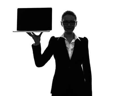one caucasian business woman holding showing computer laptop in silhouette  on white background photo