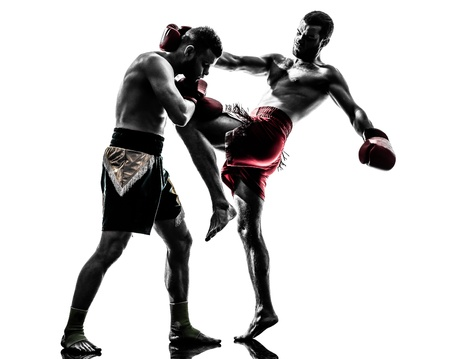 kick boxing: two caucasian  men exercising thai boxing in silhouette studio  on white background