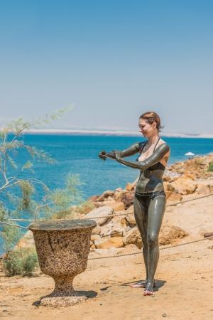 mud girl: one caucasian woman applying dead sea mud body care treatment  in jordan