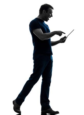 one caucasian man touchscreen digital tablet   in silhouette on white background photo