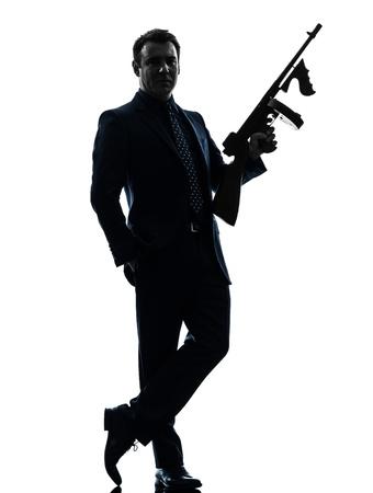 one caucasian man holding thompson machine gun  in silhouette on white background photo