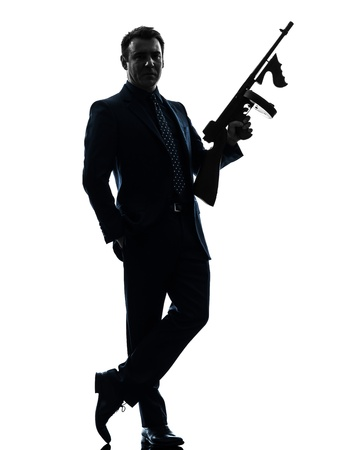 gangster with gun: one caucasian man holding thompson machine gun  in silhouette on white background