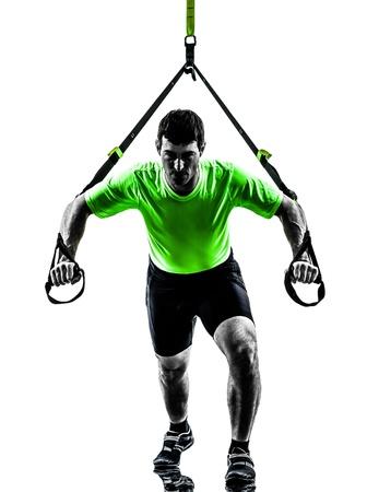 pushups: one caucasian man exercising   suspension training  trx   on white background