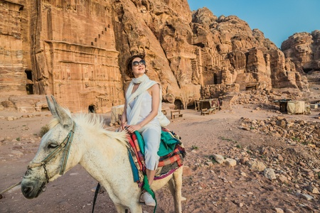 tourist riding donkey in nabatean petra jordan middle east photo