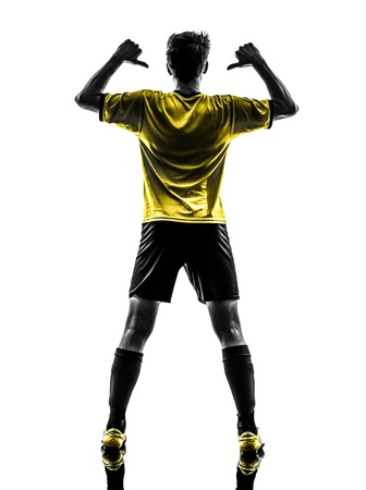 indoor soccer: one brazilian soccer football player young man rear view portrait pointing in silhouette studio  on white background