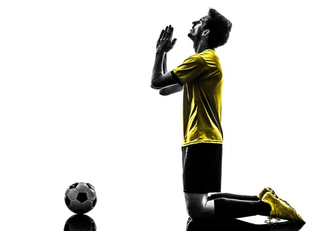 one brazilian soccer football player young man praying in silhouette studio  on white background