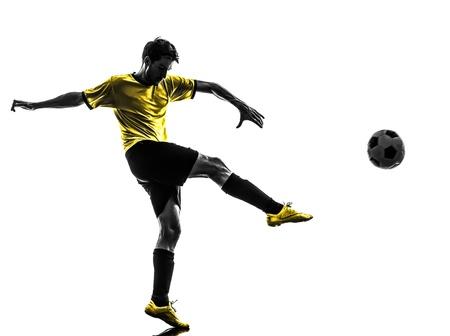 soccer: una brasileña de fútbol jugador de fútbol joven patadas en estudio de la silueta sobre fondo blanco