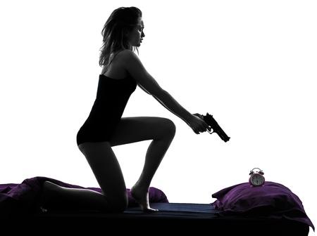 pistolas: una mujer en el estudio de cama silueta sobre fondo blanco