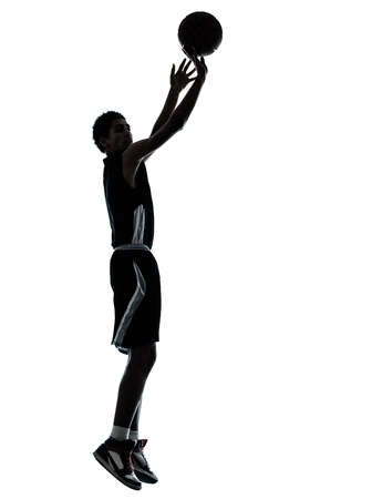 indoor sport: one young man basketball player silhouette in studio isolated on white background Stock Photo