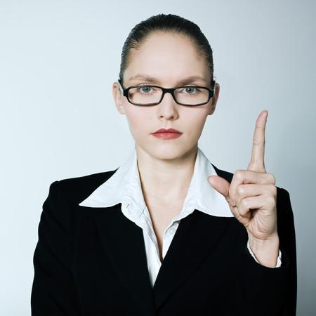 tough woman: studio shot portrait of one caucasian young  teacher nanny business woman pointing up finger