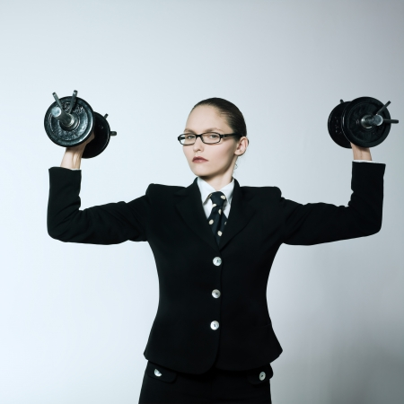 stern: studio shot portrait of one caucasian young bsuiness woman holding weights Stock Photo