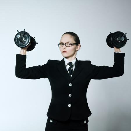 arroganza: studio shot ritratto di una giovane donna caucasica bsuiness azienda pesi