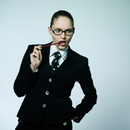 studio shot portrait of one business  woman thinking chewing pen photo