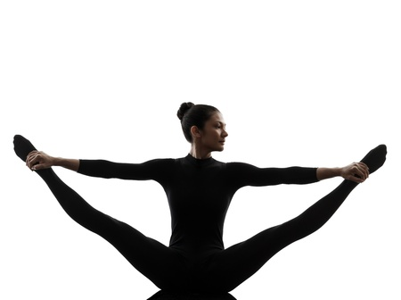 one caucasian woman practicing gymnastic yoga stretching split  in silhouette   on white background photo