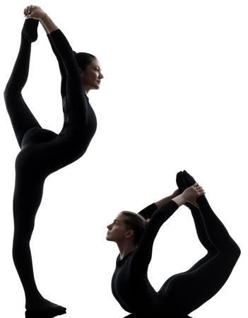 acrobacia: dos mujeres contorsionist practicar yoga gimnasia en silueta sobre fondo blanco