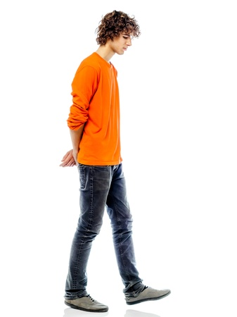 adult profile: one young man caucasian walking sad bore side view   in studio white background Stock Photo